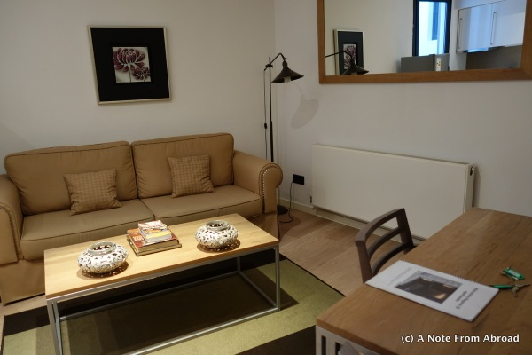 Living room with sofa bed, small table and chairs, TV