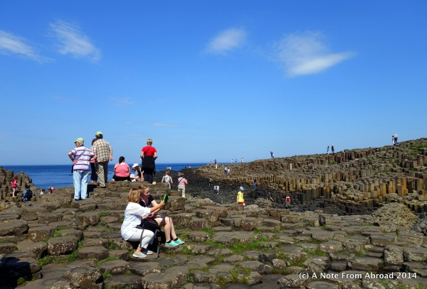 Crowds of tourists climb the rocks