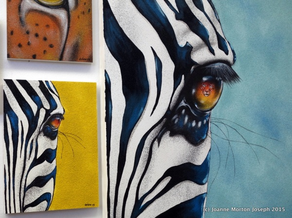 Examples of sand painting. The zebra on the right has a lion reflected in the eye.