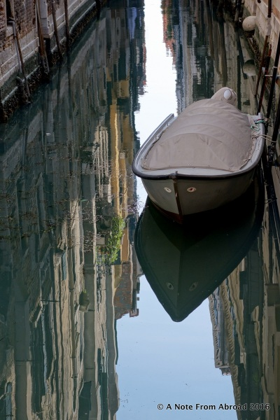 Reflections in the water. On the canals of Venice, Italy