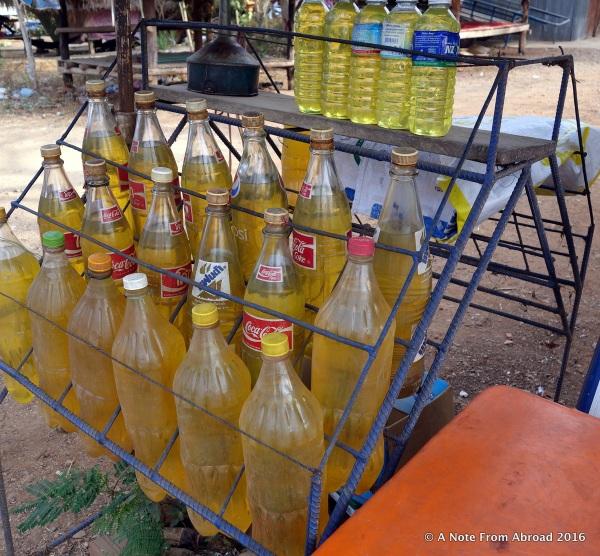 Gasoline being sold roadside in plastic soda bottles