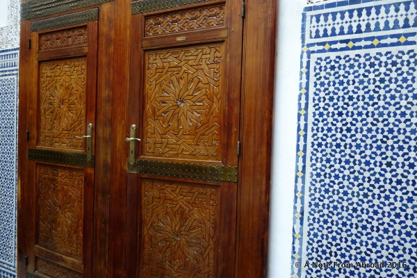 Beautifully carved doors lead into a side room and blue and white tile work
