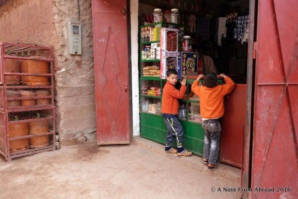 Two young boys peering into the tiny store