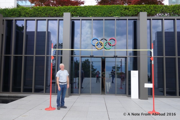 """At the main entrance, Tim standing under the high jump pole set at the current record. Tim is 6""""1"""""""