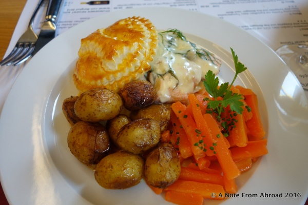 Main entree with two kinds of fish, puffed pastry, roasted potatoes and carrots