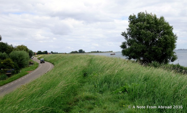 Earthen dike covered with grass with the water level higher than the road